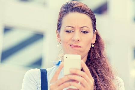 Frowning mother, annoyed at receiving SMS messages from untimely school prompts.