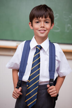 Portrait of a smiling schoolboy with a backpack in a classroom
