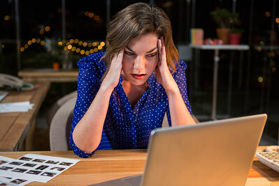 Stressed woman sitting at her desk in the office.